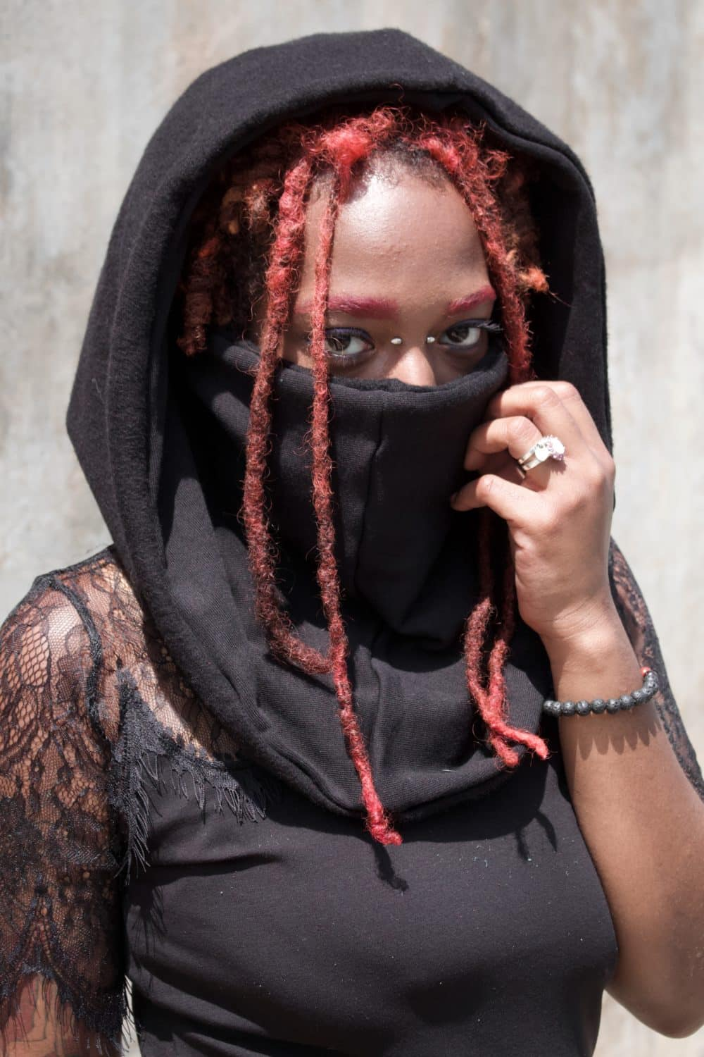 Woman in black hood with red dreads peaking through. The hood doubles as a scarf and a mask. All that is showing on her face is her eyes and forehead.